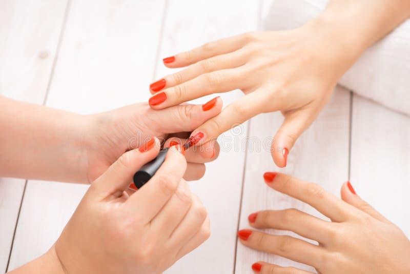Vrouw die spijkermanicure krijgen Manicure die rood nagellak toepassen op klant stock foto