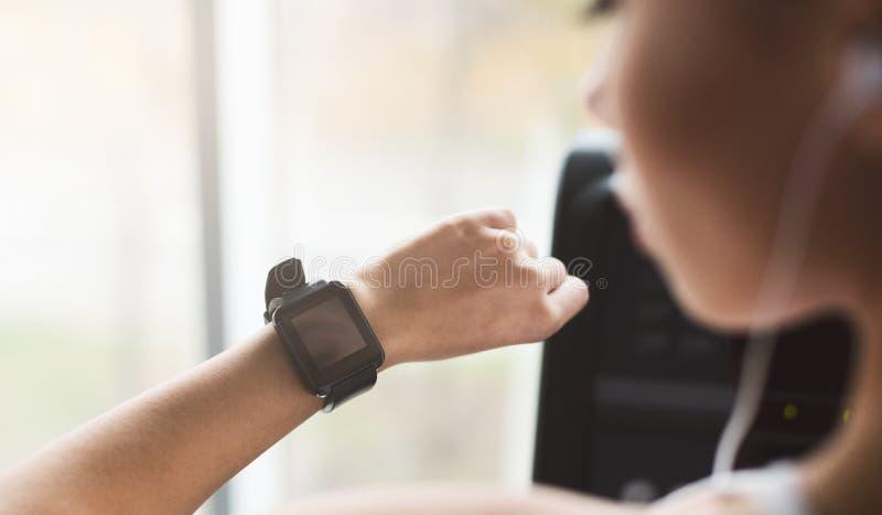 Vrouw die sport slim horloge bekijken, die cardiooefeningen doen royalty-vrije stock afbeeldingen
