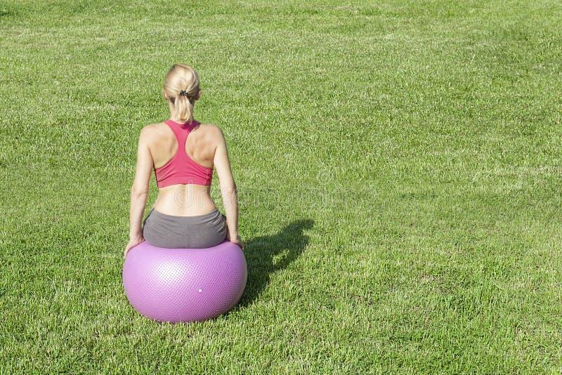 Vrouw die sporten op fitness bal op het gras doen royalty-vrije stock afbeelding