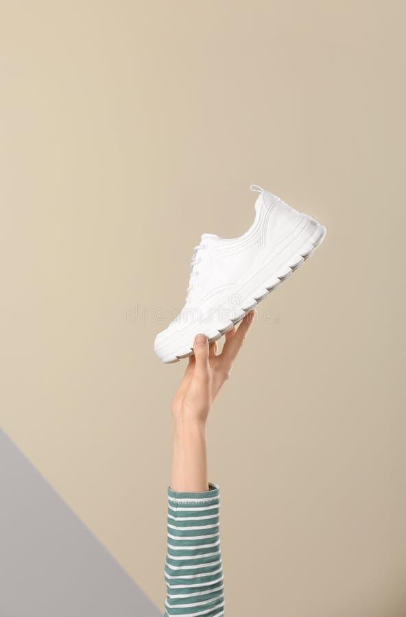 Vrouw die sportieve schoen op kleurenachtergrond houden, close-up royalty-vrije stock afbeelding