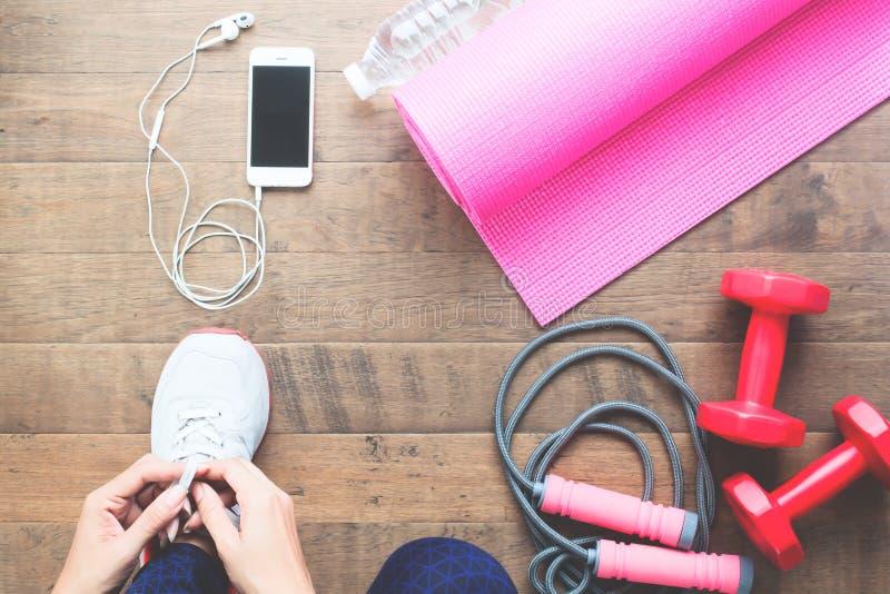 Vrouw die sportschoenen, direct hierboven met sportmateriaal verbinden op houten vloer stock afbeelding