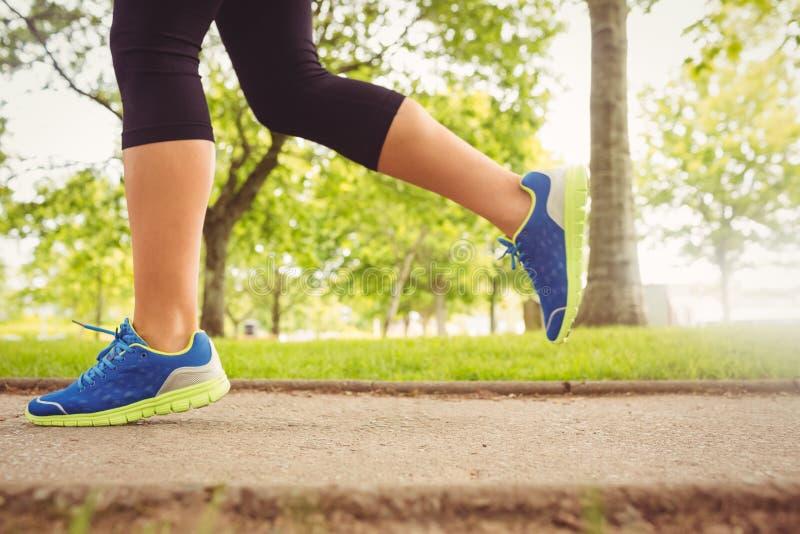 Vrouw die sportschoenen dragen die in park aanstoten stock foto