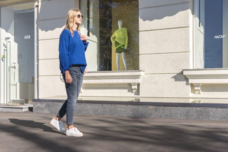 Vrouw die in stad bij de opslag lopen stock foto