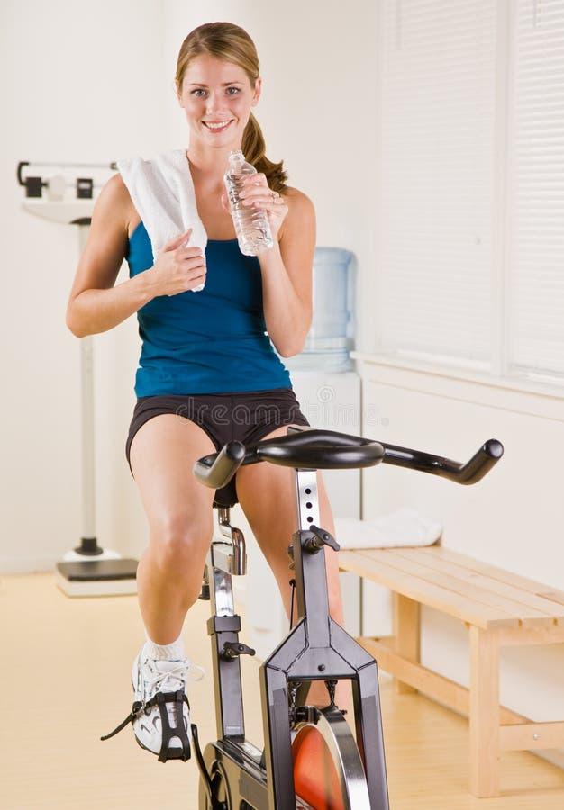 Vrouw die stationaire fiets in gezondheidsclub berijdt stock fotografie
