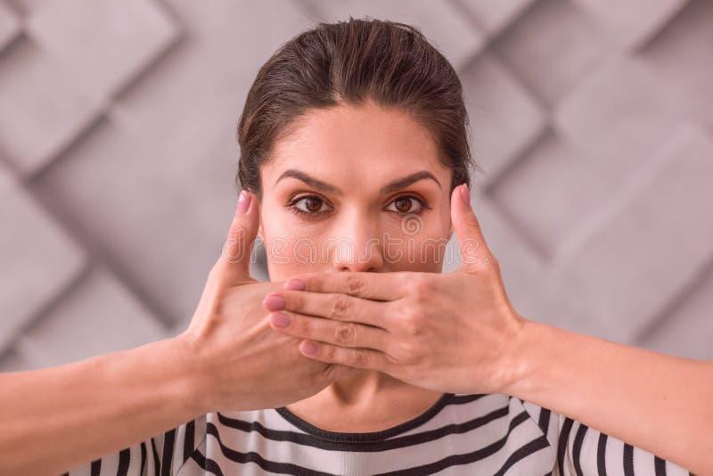 Vrouw die stilte houden door haar mond met handen te behandelen royalty-vrije stock afbeeldingen