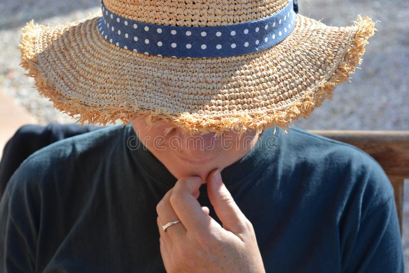 Vrouw die strohoed dragen in openlucht, hand op kin royalty-vrije stock foto