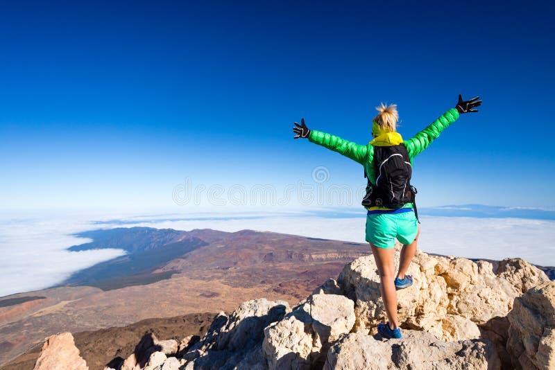 Vrouw die succes in bergbovenkant beklimmen stock foto's
