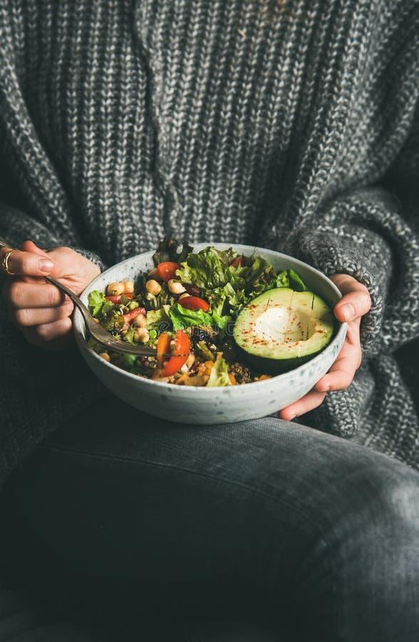 Vrouw die in sweater gezond vegetarisch diner van de kom van Boedha eten royalty-vrije stock foto