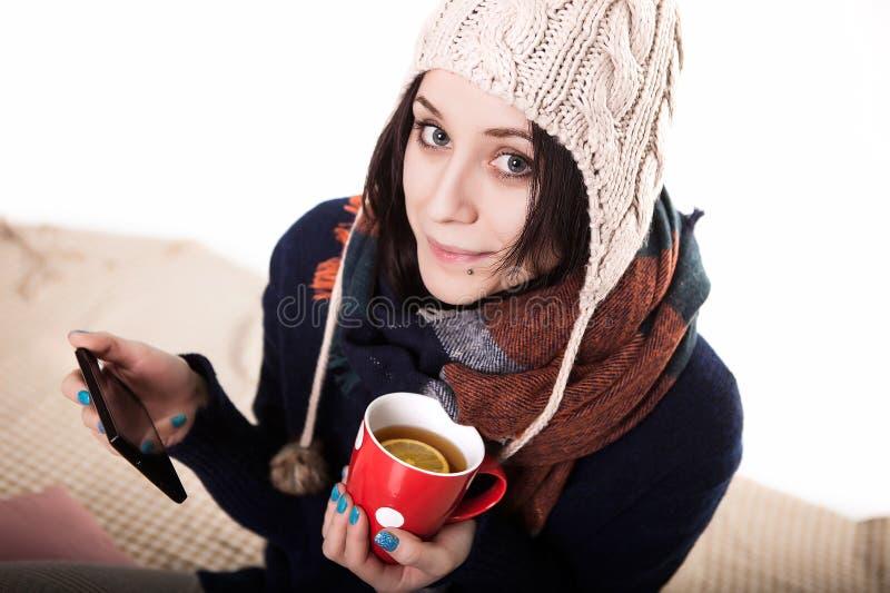 Vrouw die tablet gebruiken bij comfortabele huisatmosfeer op het bed Jonge vrouw met kopthee of koffie in handen die van vrije ti royalty-vrije stock fotografie