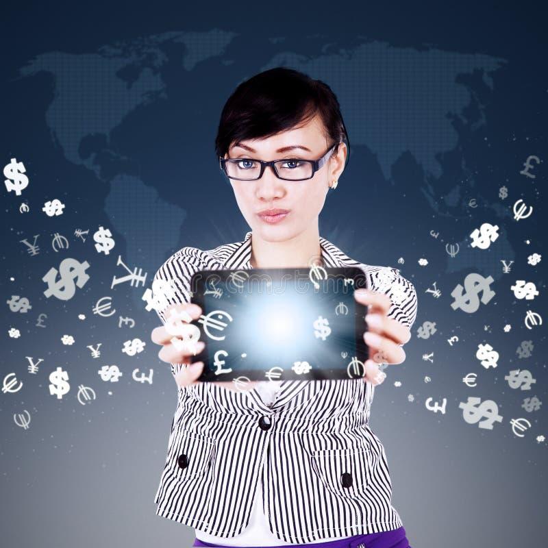 Vrouw die tablet met muntsymbolen tonen stock fotografie