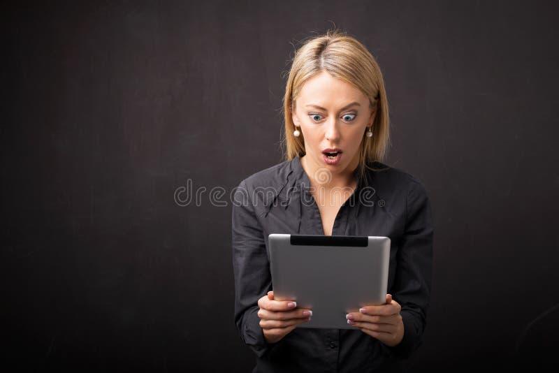 Vrouw die tablet in schok bekijken royalty-vrije stock afbeeldingen