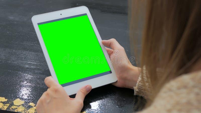 Vrouw die tabletcomputer bekijken met het groene scherm stock foto's