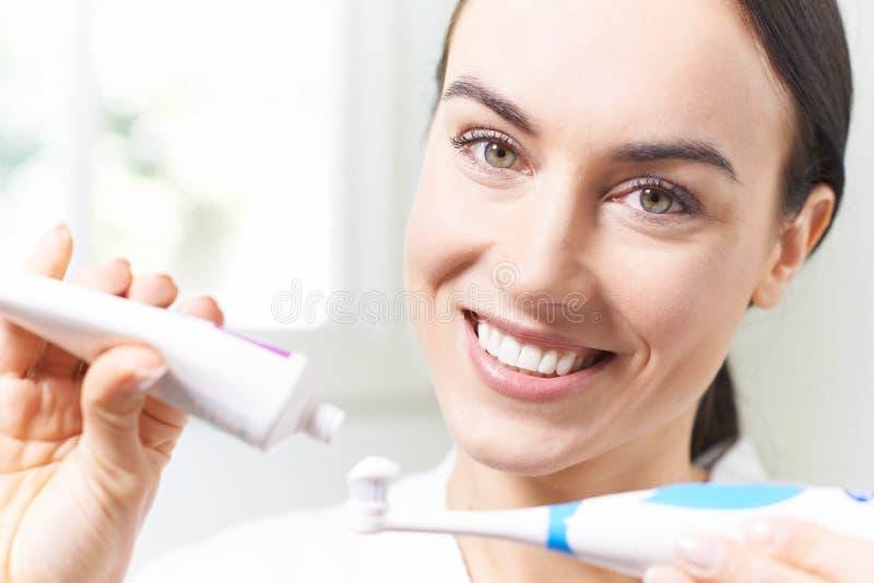 Vrouw die Tandpasta op Elektrische Tandenborstel in Badkamers drukken stock foto's