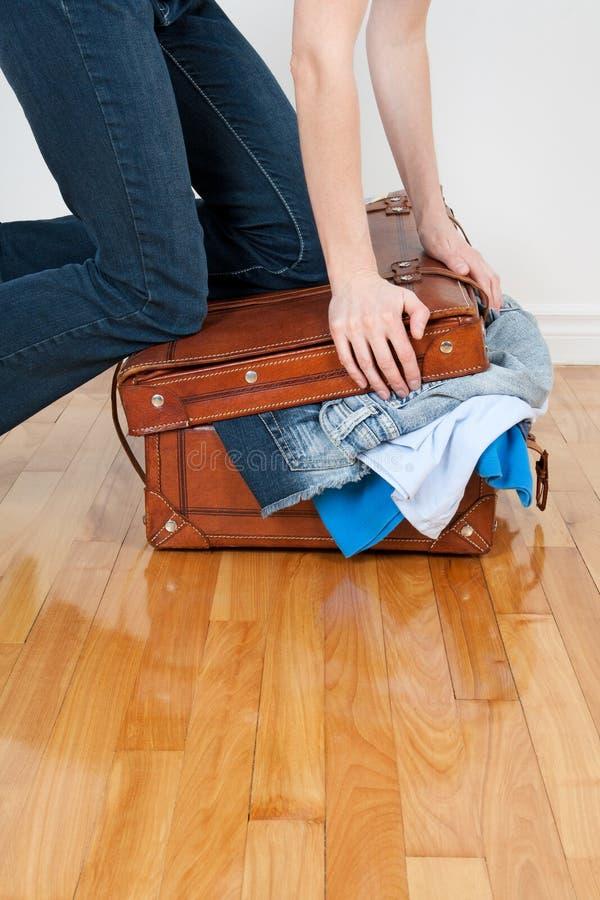 Vrouw die te vol gedaane koffer probeert te sluiten stock foto