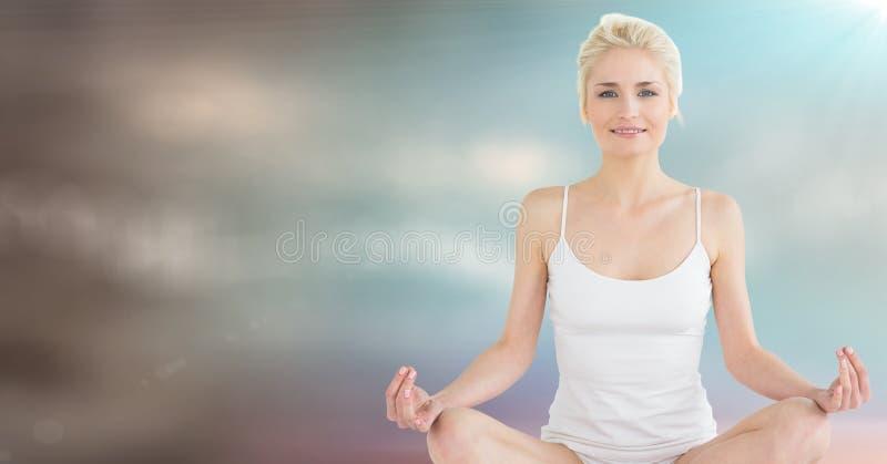 Vrouw die tegen onscherpe blauwe bruine achtergrond en gloed mediteren royalty-vrije stock afbeeldingen