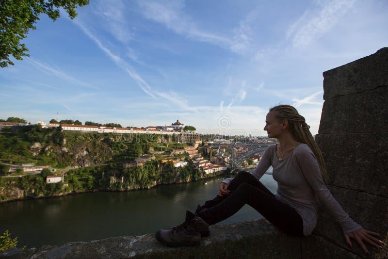 Vrouw die tegenover de Douro-rivier in Porto zitten stock fotografie