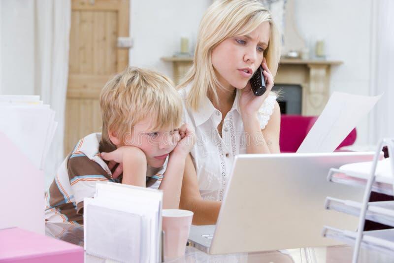 Vrouw die telefoon in bureau met laptop met behulp van stock foto's