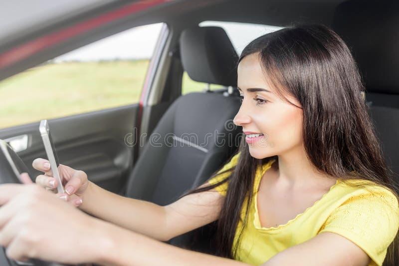 Vrouw die telefoon met behulp van bij de auto stock fotografie