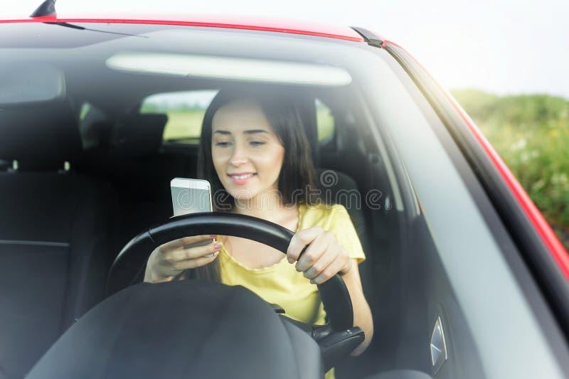 Vrouw die telefoon met behulp van bij de auto royalty-vrije stock afbeelding
