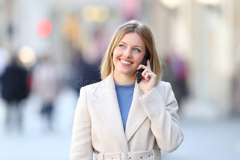 Vrouw die telefoon uitnodigen en hierboven op de straat kijken royalty-vrije stock foto