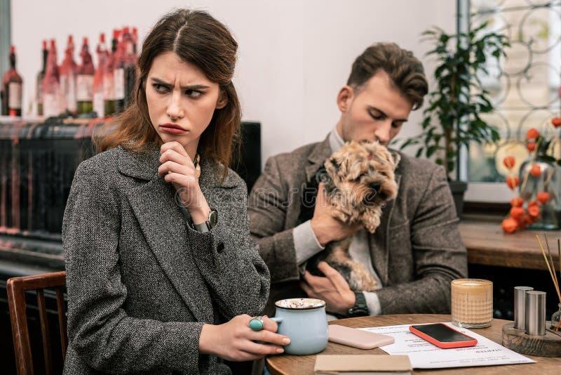 Vrouw die teleurgesteld terwijl het zitten in een koffie met haar partner kijken stock afbeeldingen