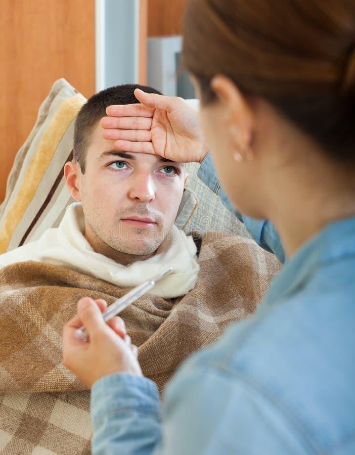 Vrouw die temperatuur voor de zieke mens meten stock afbeelding