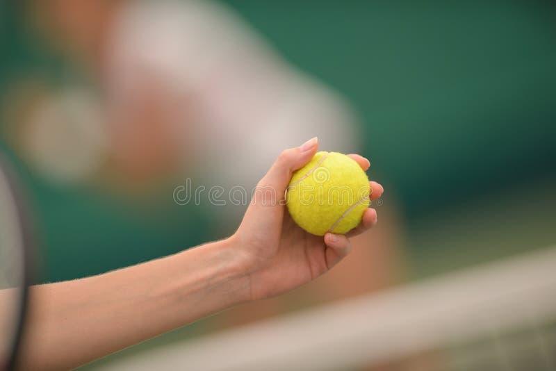 Vrouw die tennisbal ter beschikking aan u voor spel geven stock foto