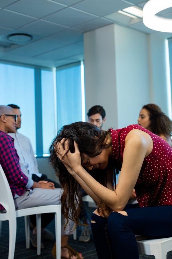 Vrouw die terwijl creatief commercieel team op achtergrond schreeuwen royalty-vrije stock foto's
