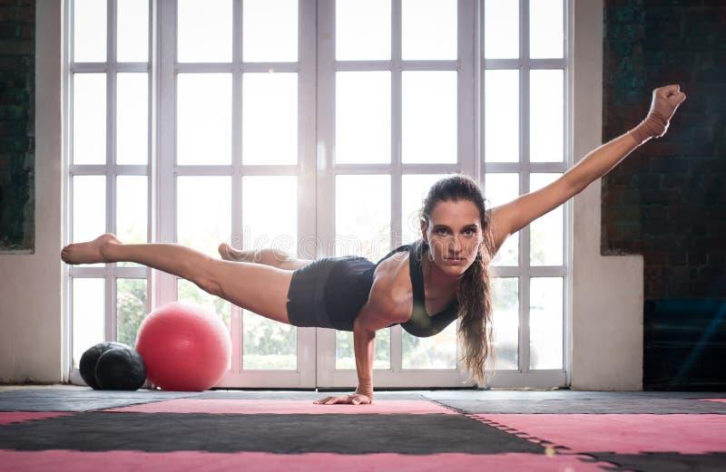 Vrouw die terwijl het doen van een één handduw die sterkte tonen in evenwicht brengen royalty-vrije stock foto's