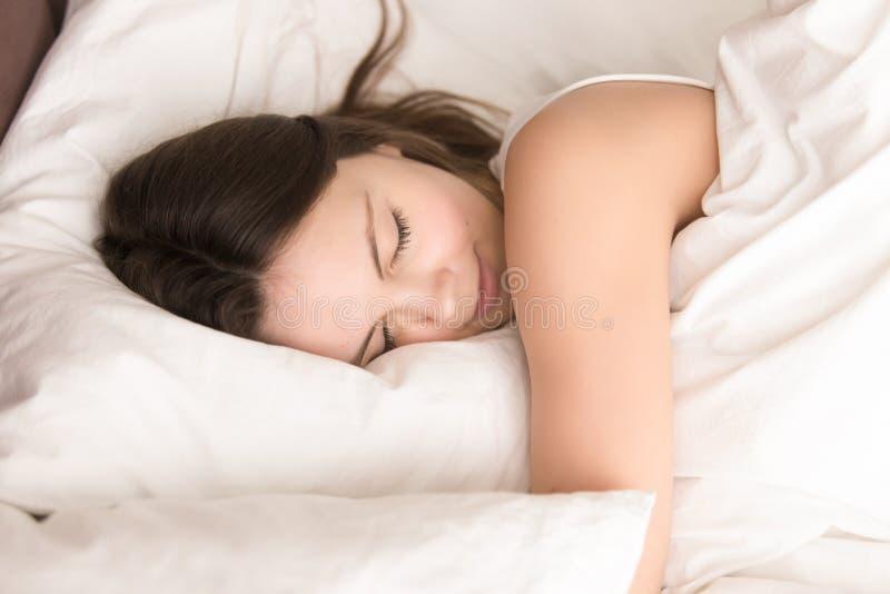 Vrouw die terwijl het koesteren van zacht hoofdkussen in bed dutten stock foto's