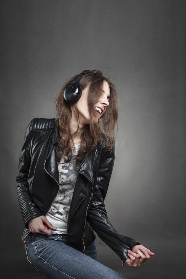 Vrouw die terwijl het luisteren aan muziek met hoofdtelefoons dansen stock foto's