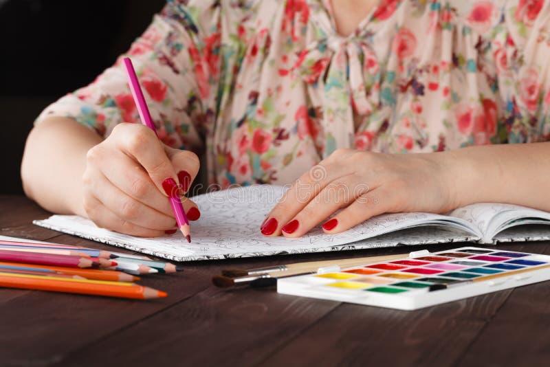 Vrouw die terwijl het schilderen volwassen kleurend boek doe ontspannen stock afbeelding