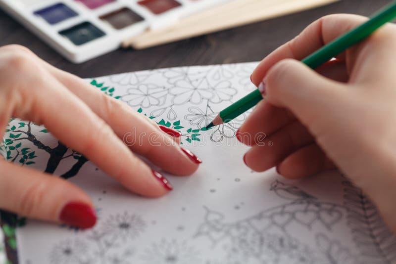 Vrouw die terwijl het schilderen volwassen kleurend boek doe ontspannen royalty-vrije stock afbeelding