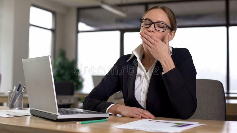 Vrouw die terwijl het werken aan die laptop geeuwen, van het monotone werk in bureau wordt vermoeid stock afbeelding