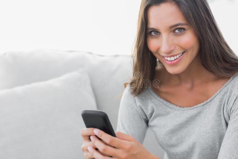 Vrouw die terwijl zij op een laag wordt gezeten texting stock fotografie