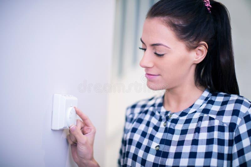 Vrouw die thuis de Controle van de Centrale verwarmingthermostaat aanpassen stock foto's