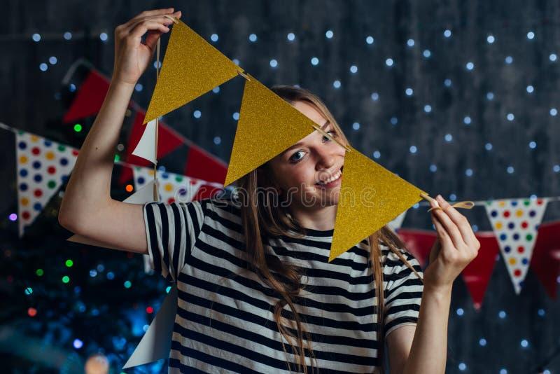 Vrouw die thuis de partijvlaggen de hangen van Kerstmislichten verfraait punten voor vierings nieuw jaar royalty-vrije stock afbeelding