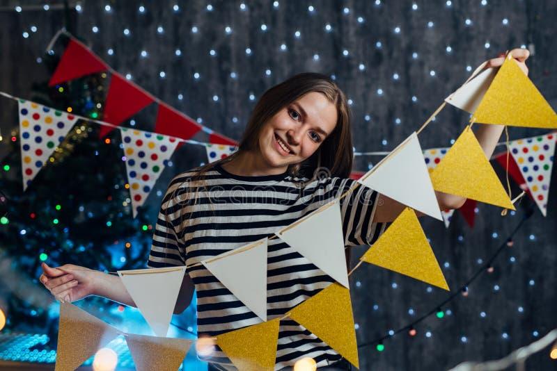 Vrouw die thuis de partijvlaggen de hangen van Kerstmislichten verfraait punten voor vierings nieuw jaar stock foto's