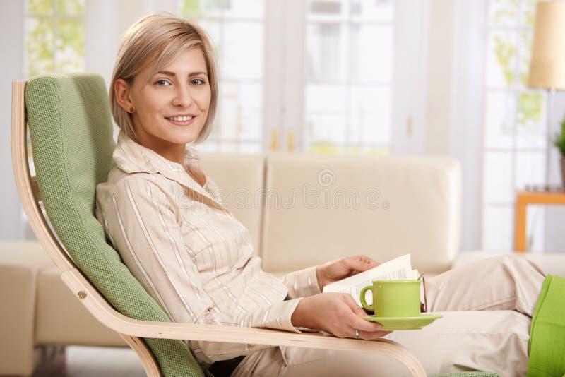 Vrouw die thuis ontspant stock fotografie