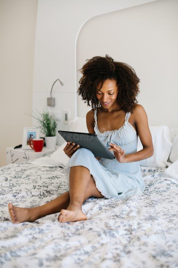 Vrouw die thuis op digitale tablet lezen royalty-vrije stock fotografie