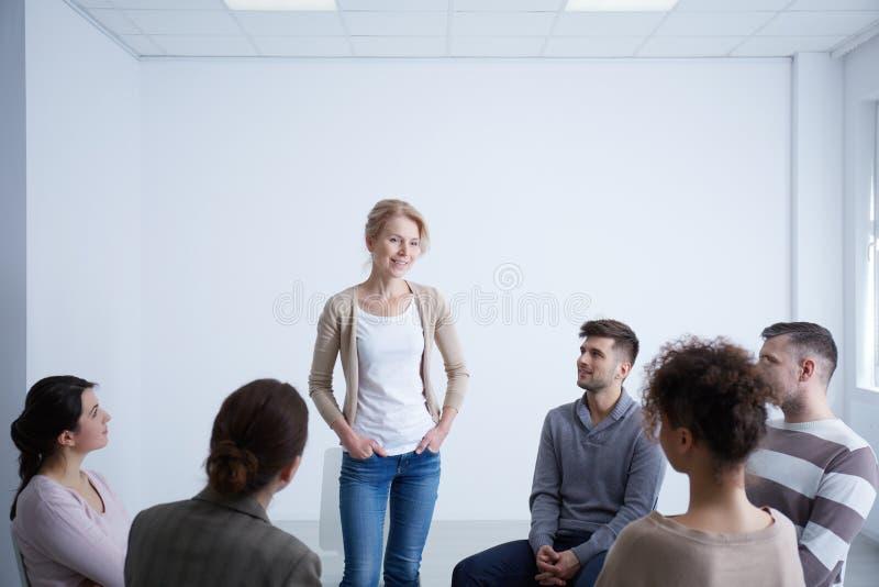 Vrouw die tijdens groepstherapie spreken stock fotografie