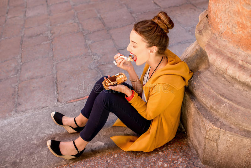 Vrouw die tiramisu in openlucht eten stock afbeelding
