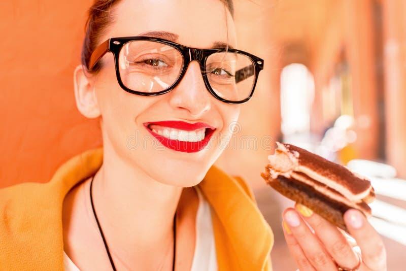 Vrouw die tiramisu in openlucht eten stock foto's