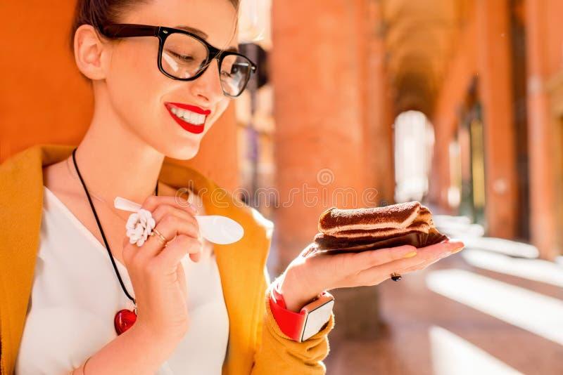 Vrouw die tiramisu in openlucht eten stock afbeeldingen