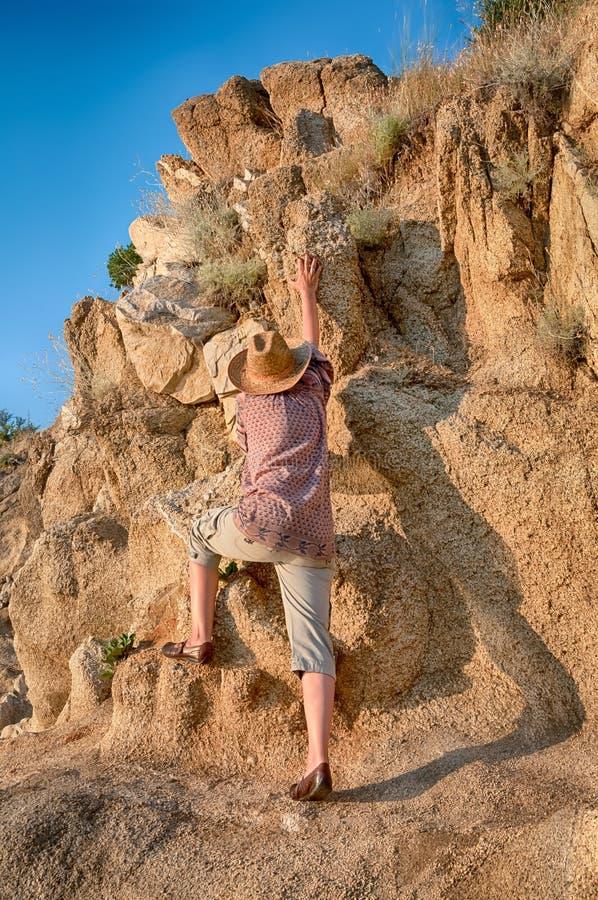 Vrouw die tot de bovenkant van de berg beklimmen royalty-vrije stock fotografie