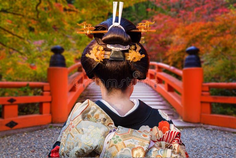 Vrouw die in traditionele kimono bij de kleurrijke esdoornbomen lopen in de herfst, Japan stock afbeelding