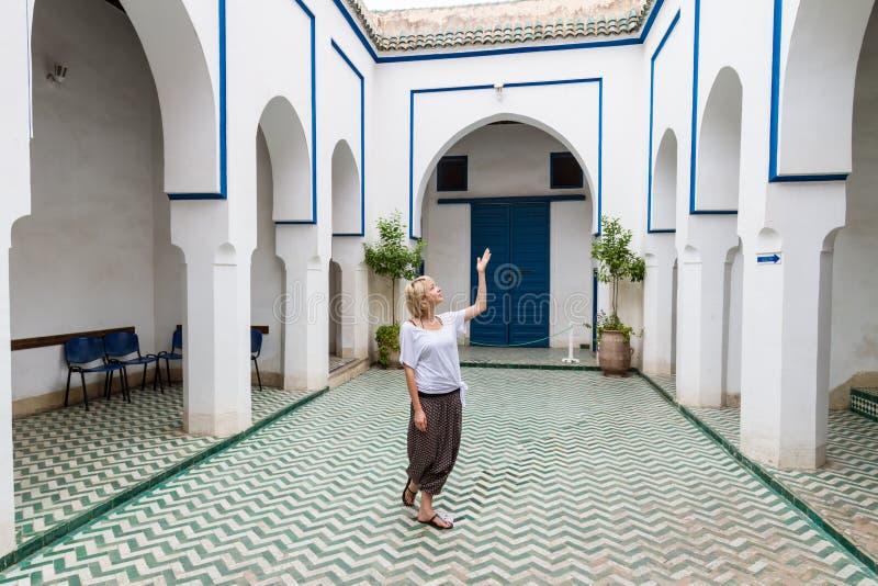 Vrouw die traditionele Marokkaanse architectuur in één van de paleizen in medina van Marrakech, Marokko bewonderen stock foto