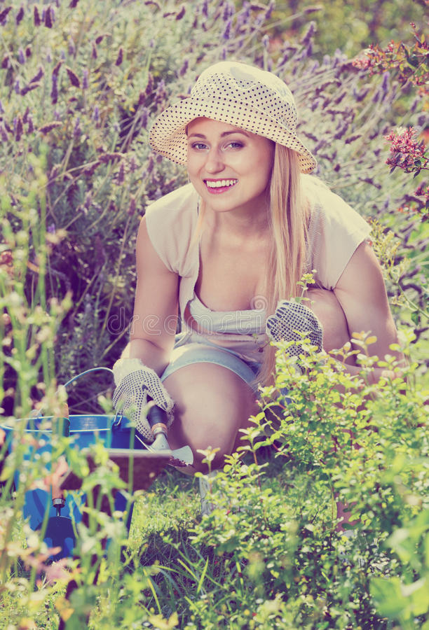Vrouw die in tuin die tuinbouwinstrumenten gebruiken aan summe werken stock afbeelding