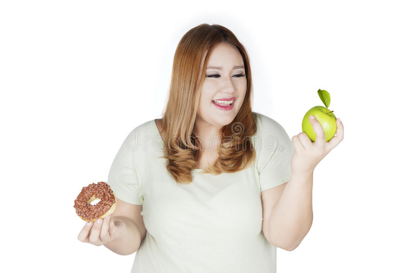 Vrouw die tussen appel en doughnut kiezen royalty-vrije stock afbeeldingen