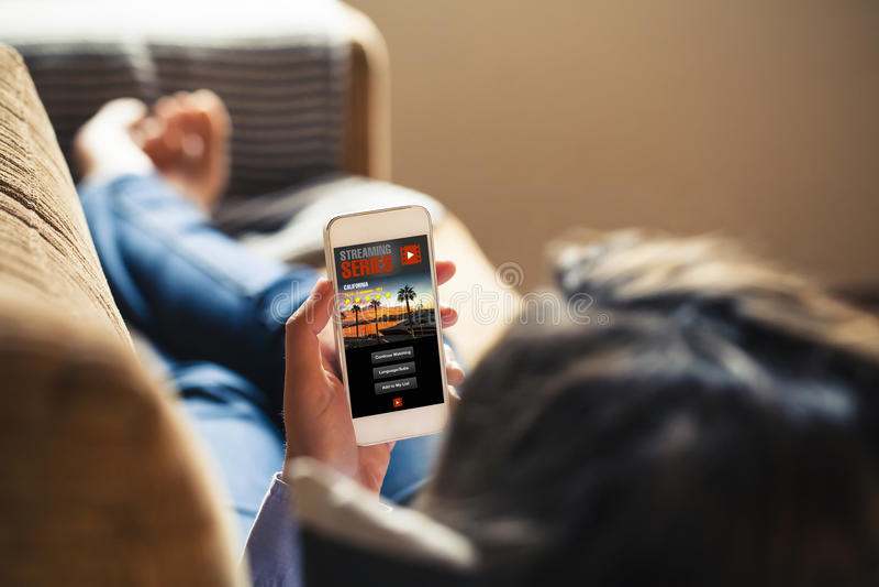 Vrouw die TV-op reeks in een mobiele telefoon app thuis letten terwijl rust royalty-vrije stock foto's